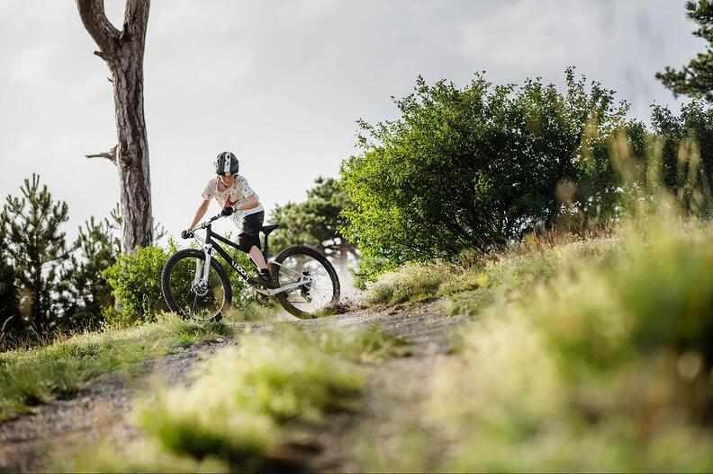 Kind bremst mit Mountainbike