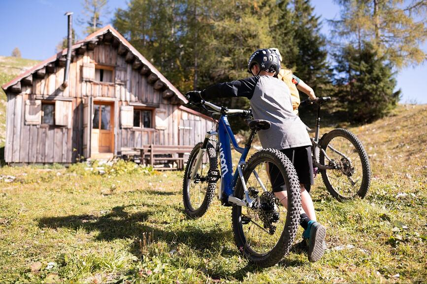 Kind mit woom E-Mountainbike am Berg