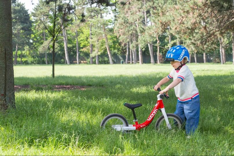 Kind hält sein rotes woom Laufrad