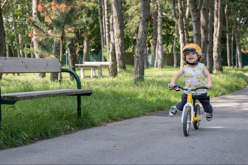 Kind auf seinem gelben woom Laufrad unterwegs