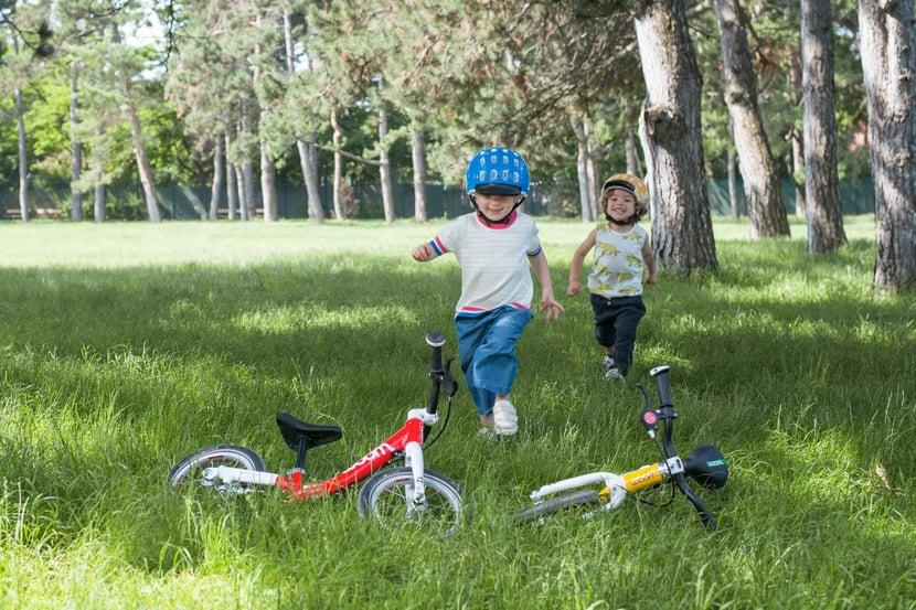 Zwei Kinder mit ihren woom Laufrädern