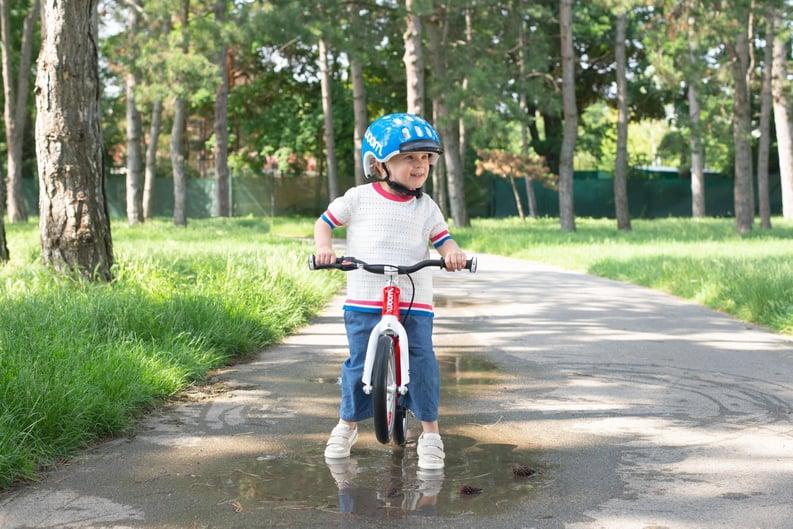 Kind mit woom Laufrad in Lacke