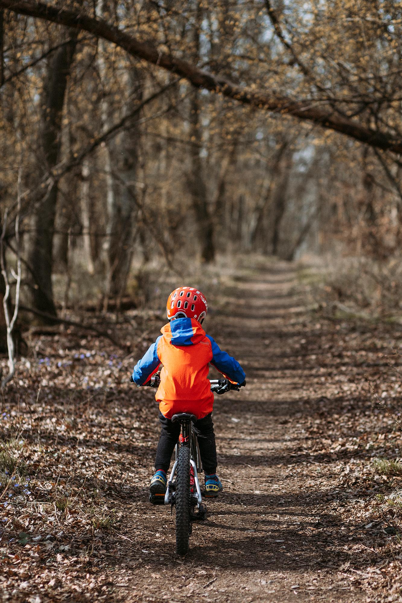 Kind mit woom Fahrrad im Herbst-Wald